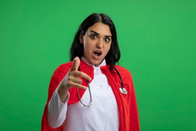 Przestraszona młoda dziewczyna superbohatera na sobie szlafrok medyczny ze stetoskopem, pokazując gest na białym tle na zielono
