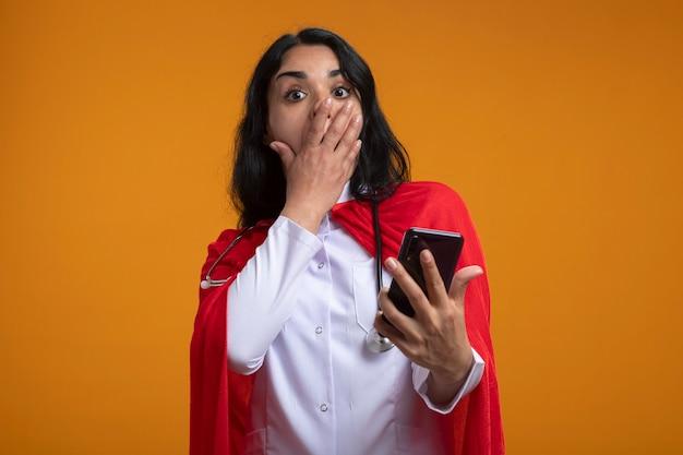 Przestraszona młoda dziewczyna superbohatera ubrana w szlafrok medyczny ze stetoskopem, trzymając telefon zakryte usta ręką odizolowaną na pomarańczowej ścianie