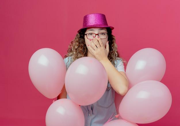Przestraszona młoda dziewczyna w okularach i różowym kapeluszu stojąca wśród balonów i zakryte usta na białym tle na różowej ścianie