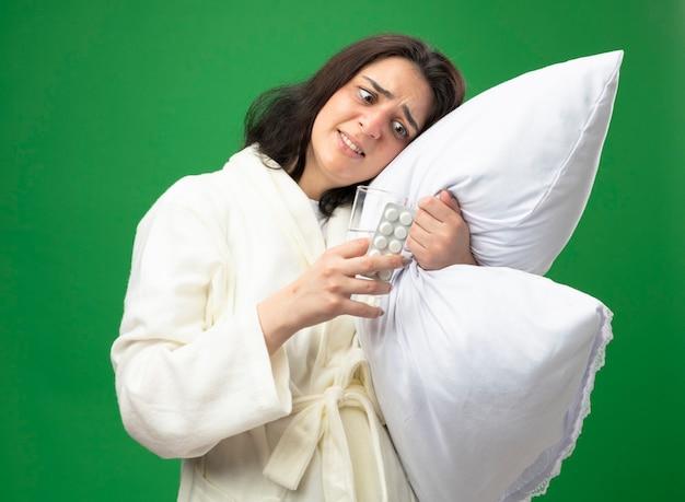 Przestraszona młoda kaukaska chora dziewczyna ubrana w szatę przytulającą poduszkę kładąc na niej głowę trzymając szklankę wody i paczkę tabletek medycznych, patrząc na nie na białym tle na zielonym tle