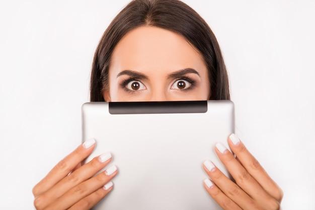 Przestraszona młoda kobieta chowa twarz za tabletem