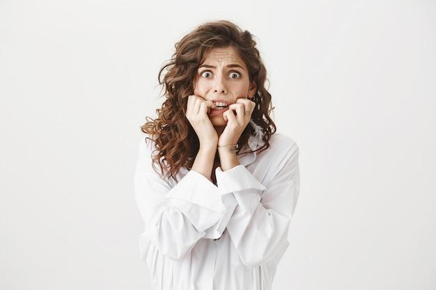 Przestraszona młoda kobieta gryzie paznokcie, drżąc ze strachu