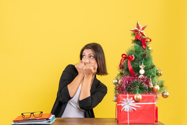 Przestraszona młoda kobieta, patrząc na coś siedzącego przy stole w pobliżu udekorowanej choinki w biurze na żółto