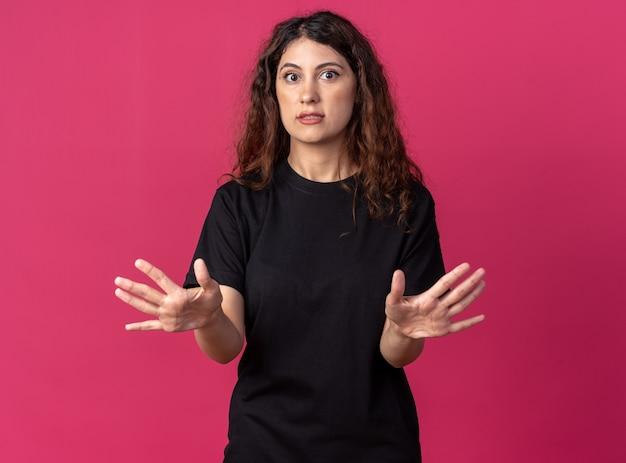 Przestraszona młoda ładna kobieta patrząca z przodu, wykonująca gest odmowy na białym tle na szkarłatnej ścianie