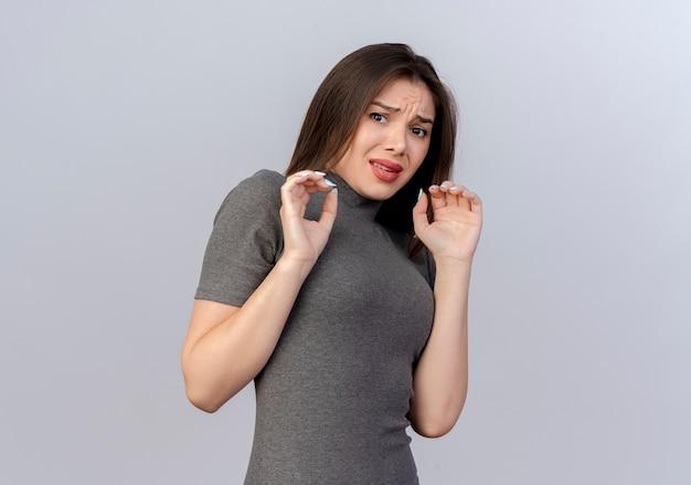 Przestraszona młoda ładna kobieta trzymając ręce w powietrzu patrząc na kamery na białym tle na białym tle z miejsca na kopię