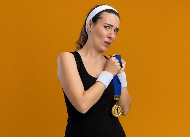 Przestraszona młoda ładna sportowa kobieta nosząca opaskę i opaski, patrząca na przedni medal trzymający na białym tle na pomarańczowej ścianie z miejscem na kopię