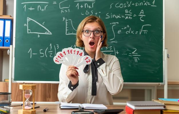 Przestraszona młoda nauczycielka w okularach siedzi przy stole z przyborami szkolnymi, trzymając w ręku kilka fanów, kładących dłoń na policzku w klasie