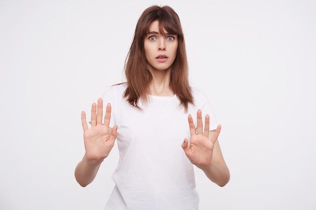 Przestraszona młoda niebieskooka ciemnowłosa kobieta trzyma uniesione dłonie przed sobą i wygląda przerażająco, ubrana w białą podstawową koszulkę, stojąc nad białą ścianą