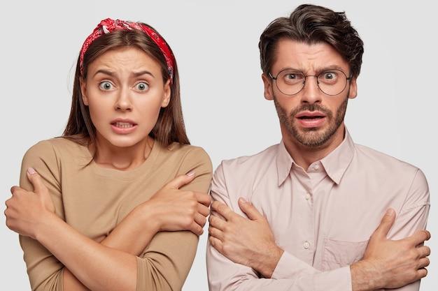 Przestraszona młoda para pozuje przy białej ścianie