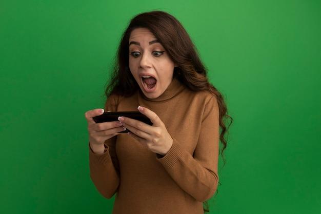 Przestraszona młoda piękna dziewczyna gra na telefon na białym tle na zielonej ścianie