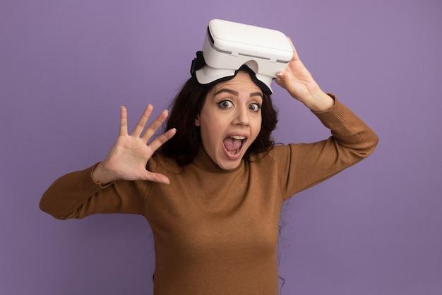 Przestraszona młoda piękna dziewczyna nosi i trzyma zestaw słuchawkowy vr na białym tle na fioletowej ścianie