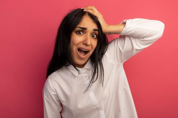 Przestraszona młoda piękna dziewczyna ubrana w białą koszulkę kładąc rękę na głowie na różowym tle