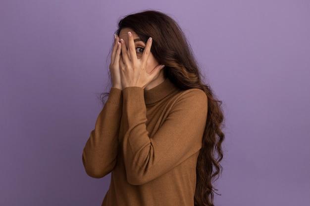 Przestraszona młoda piękna dziewczyna ubrana w brązowy sweter z golfem zakryła twarz rękami odizolowanymi na fioletowej ścianie