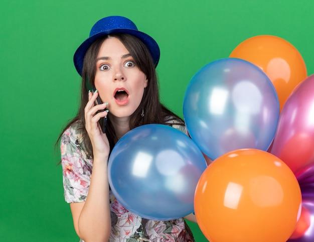 Przestraszona młoda piękna dziewczyna w kapeluszu imprezowym trzymająca balony rozmawia przez telefon