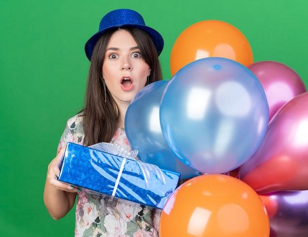Przestraszona młoda piękna dziewczyna w kapeluszu imprezowym trzymająca balony z pudełkiem na prezent