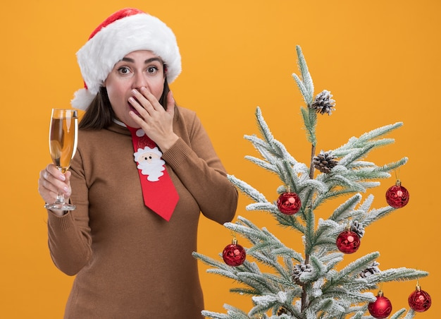 Przestraszona młoda piękna dziewczyna w świątecznym kapeluszu z krawatem stojąca w pobliżu choinki trzymająca kieliszek szampana pokryte usta ręką odizolowaną na pomarańczowej ścianie