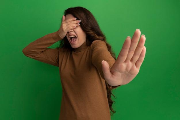 Przestraszona młoda piękna dziewczyna zakryła oczy rękami i wyciągnęła rękę na białym tle na zielonej ścianie