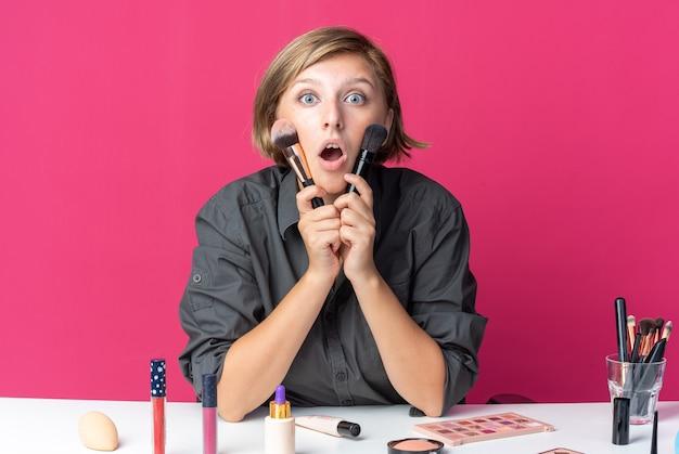 Przestraszona młoda piękna kobieta siedzi przy stole z narzędziami do makijażu, trzymając pędzel do pudru wokół twarzy