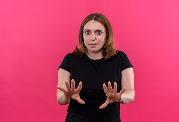 Przestraszona młoda przypadkowa kobieta gestykuluje nie na odosobnionej różowej przestrzeni z kopią miejsca