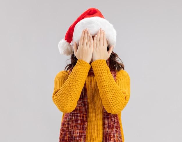 Przestraszona młoda słowiańska dziewczyna z czapką mikołaja i szalikiem wokół szyi, zamykając twarz rękami
