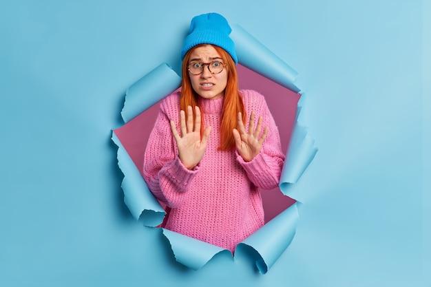 Przestraszona nerwowa kobieta w dzianinowym swetrze i czapce wykonuje gest stop i próbuje się bronić, wpatrując się w coś nieprzyjemnego lub przerażającego.