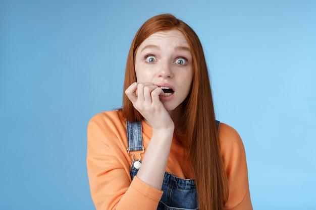 Przestraszona niepewna niespokojna młoda drżąca rudowłosa dziewczyna z szeroko otwartymi oczami wpatrująca się w intensywne emocjonalne gryzące paznokcie, fan martw się ulubioną postacią serialu telewizyjnego umiera stojąc nerwowo na niebieskim tle.
