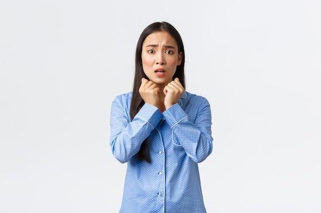 Przestraszona nieśmiała azjatka spanikowana, niespokojna i przestraszona, trzęsąca się jak stojąca w niebieskiej piżamie