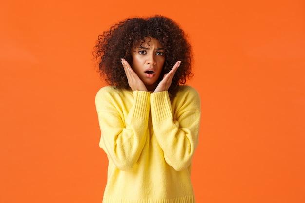 Przestraszona, nieśmiała i niepewna, śliczna młoda dziewczyna z fryzurą w stylu afro, żółtym swetrem, sapiąca, zszokowana i zmartwiona, dotykająca i wpatrująca się w panikę, czująca się przerażona, stojąca na pomarańczowej ścianie.