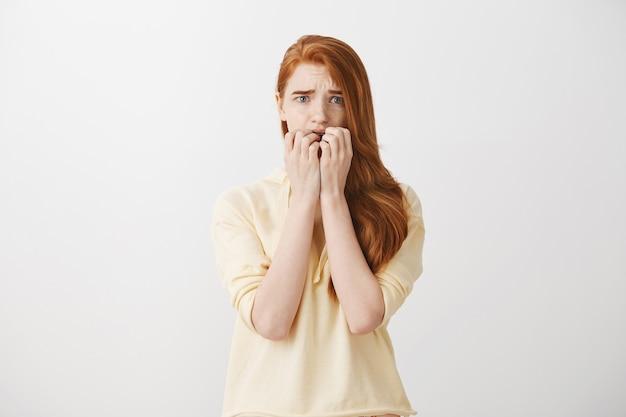 Przestraszona nieśmiała ruda dziewczyna wyglądająca na przestraszoną