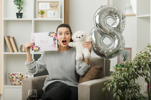 Przestraszona piękna dziewczyna w szczęśliwy dzień kobiet trzymająca kartkę z życzeniami z misiem siedzącym na fotelu w salonie