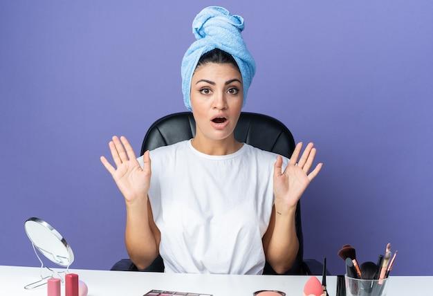 Przestraszona piękna kobieta siedzi przy stole z narzędziami do makijażu owiniętymi włosami w ręcznik pokazując gest zatrzymania