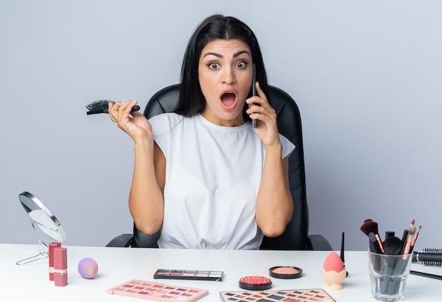 Przestraszona piękna kobieta siedzi przy stole z narzędziami do makijażu, trzymając grzebień, mówi przez telefon