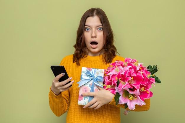 Przestraszona piękna młoda dziewczyna trzyma prezenty z telefonem