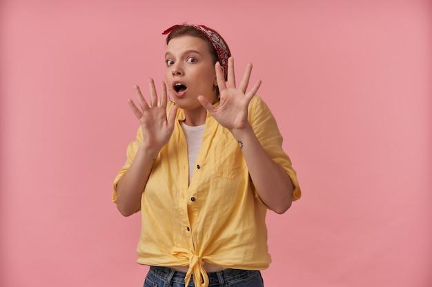 Przestraszona, przerażona młoda kobieta w żółtej koszuli z opaską na głowie, broniąca się rękami przed wrogami nad różową ścianą