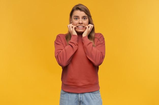 Przestraszona, przestraszona młoda kobieta w zwykłym ubraniu trzyma dłonie na policzkach i wygląda na zmartwioną przez żółtą ścianę