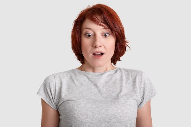 Przestraszona rudowłosa kobieta wpatruje się w osłupienie w podłogę, ubrana w szarą koszulkę