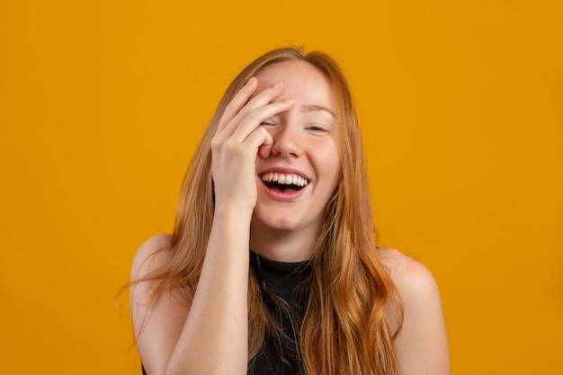 Przestraszona rudowłosa młoda kobieta na żółtej ścianie chowa się za dłońmi, przerażona rudowłosa twarz dziewczyny spogląda przez palce, ciekawa kobieta czuje przestraszony zerkanie.