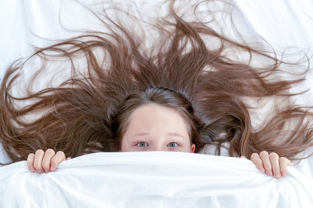 Przestraszona śliczna mała dziewczynka leży w łóżku z kocem