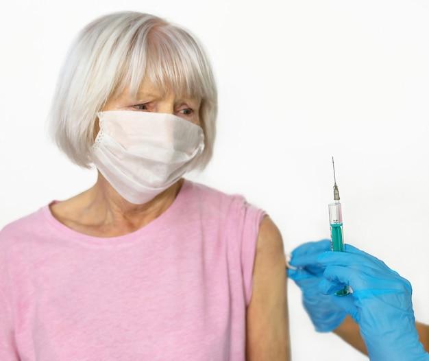 Przestraszona starsza kobieta w masce i lekarze ręce w rękawiczkach medycznych ze strzykawką podczas szczepienia