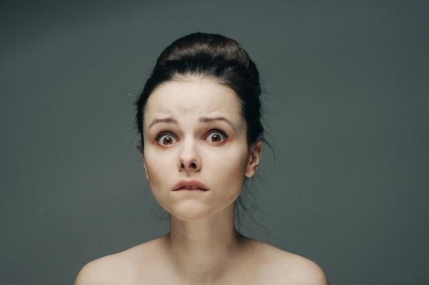 Przestraszona twarz kobiety nagie ramiona fryzura szara modelka