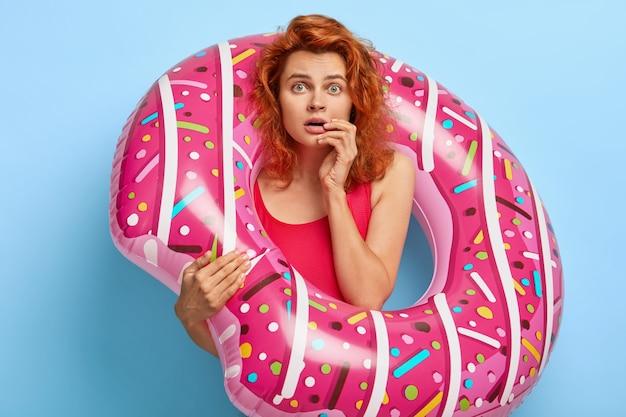 Przestraszona urocza modelka wpatruje się w kamerę, trzyma nadmuchany pierścień do pływania, ubrana w czerwony kostium kąpielowy, zszokowana zepsutymi wakacjami