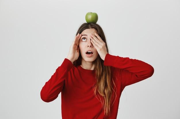 Przestraszona zaniepokojona dziewczyna otwiera oczy i patrzy na cel jabłka na głowie