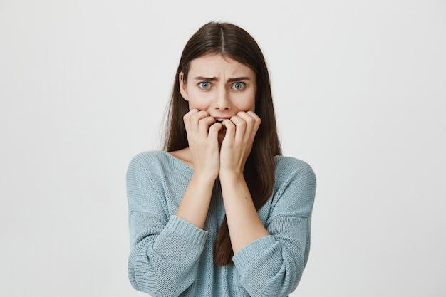 Przestraszona zaniepokojona kobieta gryzie paznokcie, marszczy brwi i przestraszona