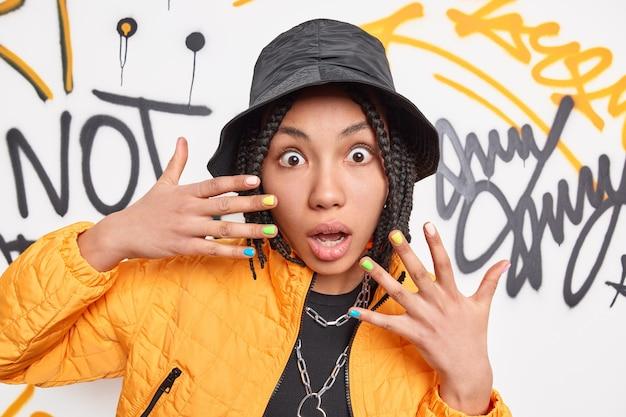 Przestraszona, zaskoczona etniczna kobieta z dredami, która trzyma ręce uniesione, spędza czas z przyjaciółmi w miejskim miejscu, pozuje na ścianie graffiti, ubrana w modne ubrania