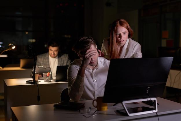 Przestraszona zmartwiona niespokojna ruda kobieta jest niezadowolona z pracy mężczyzny w biurze, kobieta jest zirytowana patrząc na ekran komputera pc. widok z boku. późno w nocy w biurze