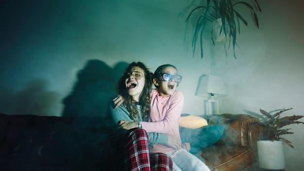 Przestraszone dziewczyny oglądające telewizję