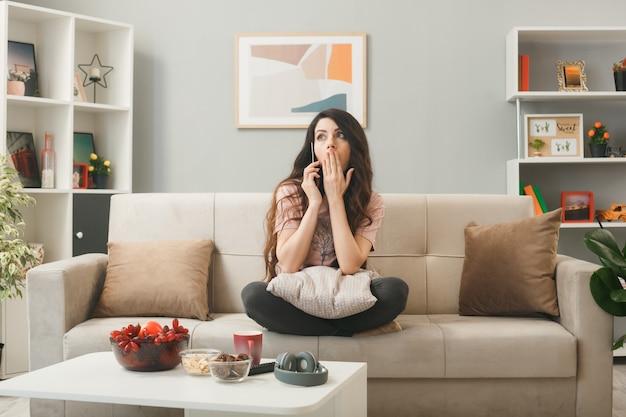 Przestraszone, zakryte usta ręką, młoda dziewczyna rozmawia przez telefon, siedząc na kanapie za stolikiem kawowym w salonie