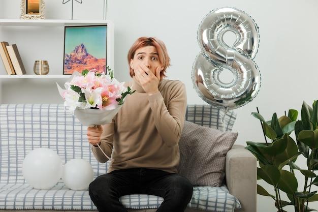 Przestraszone, zakryte usta ręką przystojnego faceta na szczęśliwy dzień kobiet trzymający bukiet siedzący na kanapie w salonie