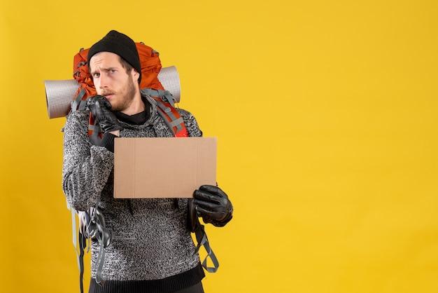 Przestraszony autostopowicz w skórzanych rękawiczkach i plecaku z pustym kartonem