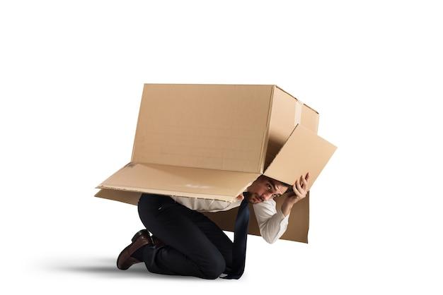 Przestraszony biznesmen chowa się pod kartonem